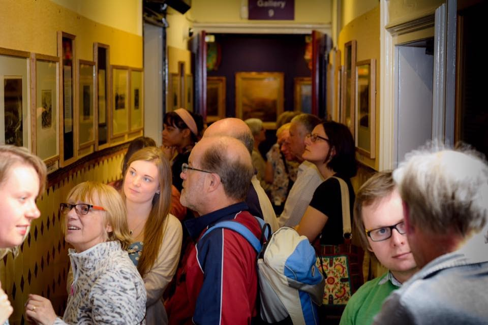 A gathering of people of all ages stand in a corridor, looking at the framed poems and etchings which are fixed in rows along either wall.