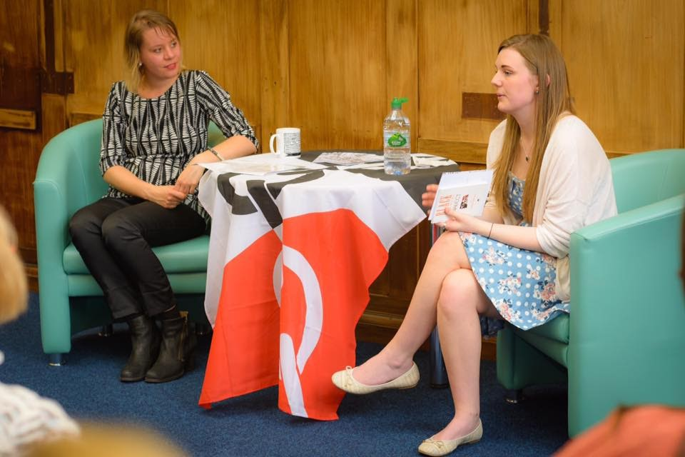Two young women (Jorine and Nellie) sit on either side of a table, which is draped with a Black Country flag. Jorine is looking at Nellie, who is addressing a group of people out of shot.