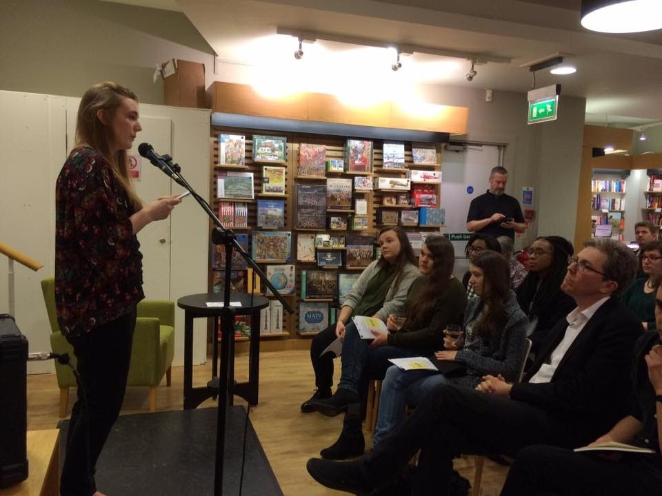 A young woman stands on a stage, behind a mic, reading to a room of seated people, only the first row can be seen. The backdrop is a bookshop.