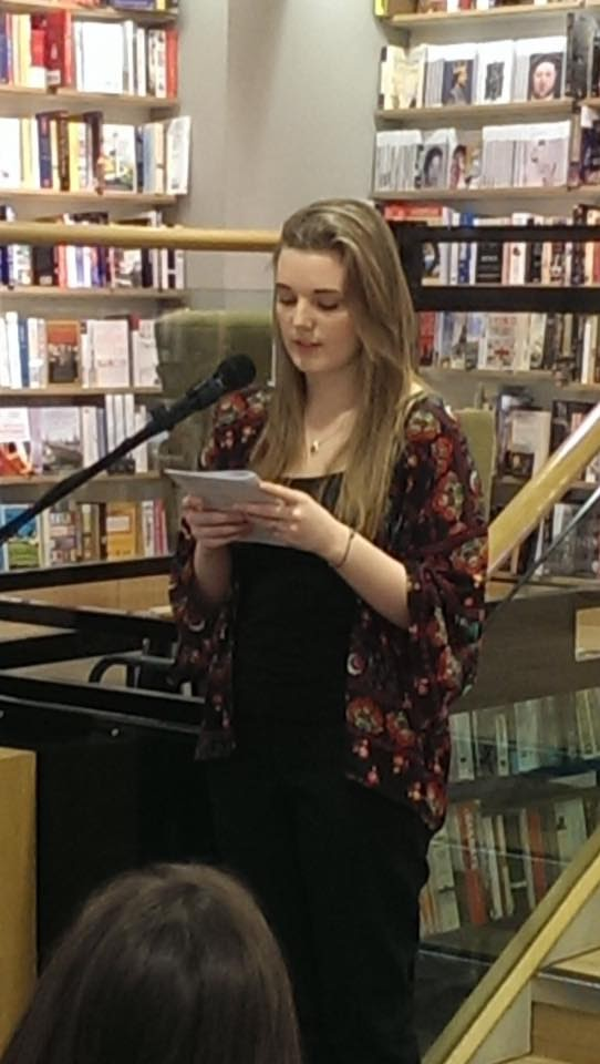 A young woman reads from behind a mic, holding a booklet in her hands. The backdrop is a bookshop.