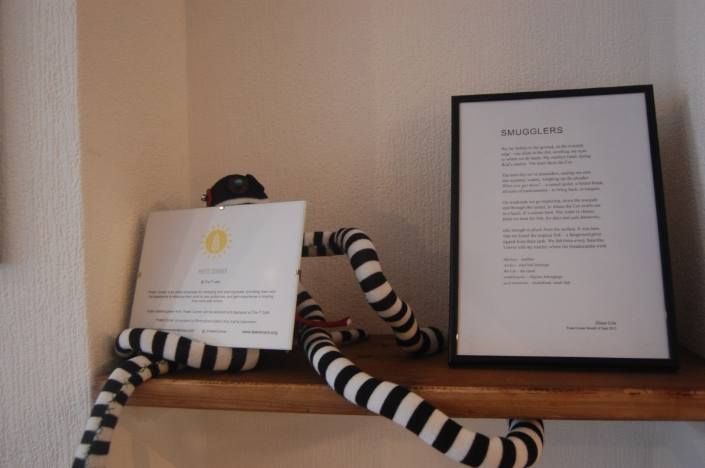 A framed poem, titled 'Smugglers', sits on a shelf next to a knitted monkey, striped black-and-white, with long arms and legs. A framed bio sits on the monkey's lap.