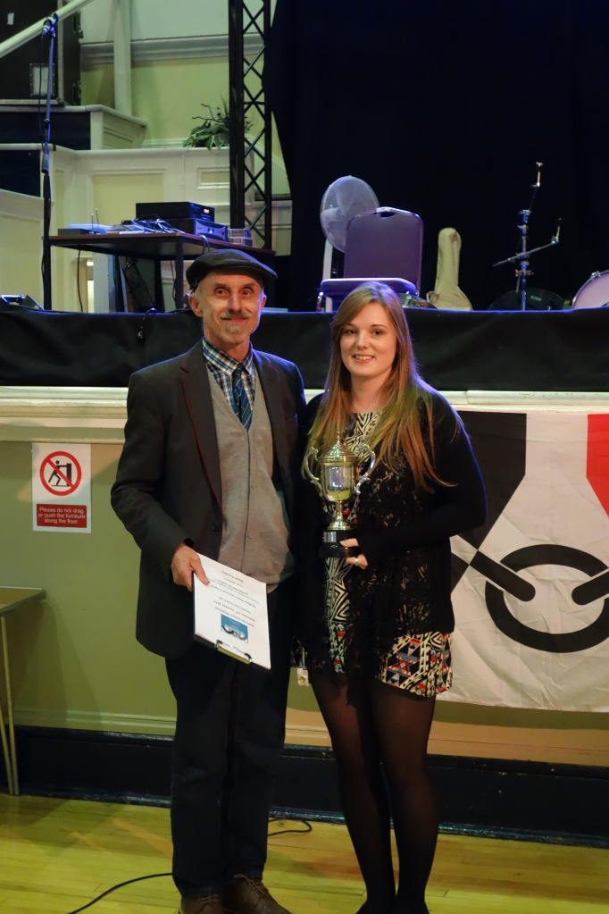 A young woman (Nellie) and an older man (Billy) stand side by side, smiling at the camera, in front of the stage which is dressed with a Black Country flag. Nellie holds the silver trophy in front of her.