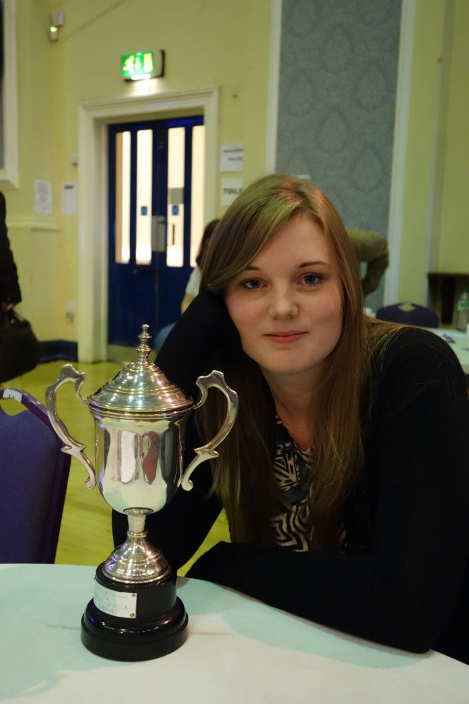 A young woman is sat, semi-smiling at the camera, her jaw resting on her hand. On the table in front of her there is a large silver trophy.