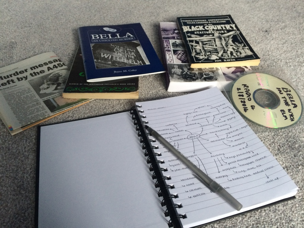 A notebook open at the first page, with words and phrases drawn on in a mindmap. The notebook is surrounded by books, newspaper clippings and a CD about 'Bella and the Wych Elm'.
