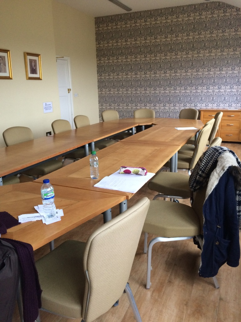 A classroom set up with chairs around a long boardroom table. Some papers, pens, and water bottles on the table.