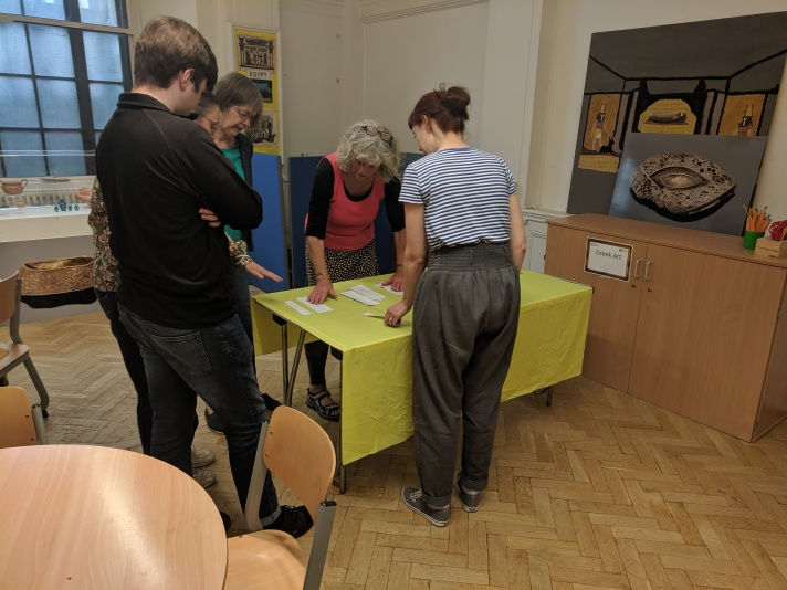 Five adults stand around a table, arranging slips of paper into an order, during a writing exercise.