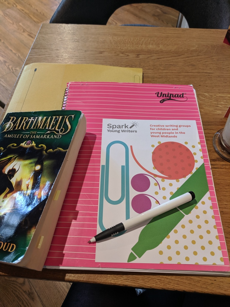A yellow paper folder, a pink Unipad notepad, a Spark Young Writers leaflet, a copy of the YA novel Bartimaeus by Jonathan Stroud, and a pen, laid out on a table.
