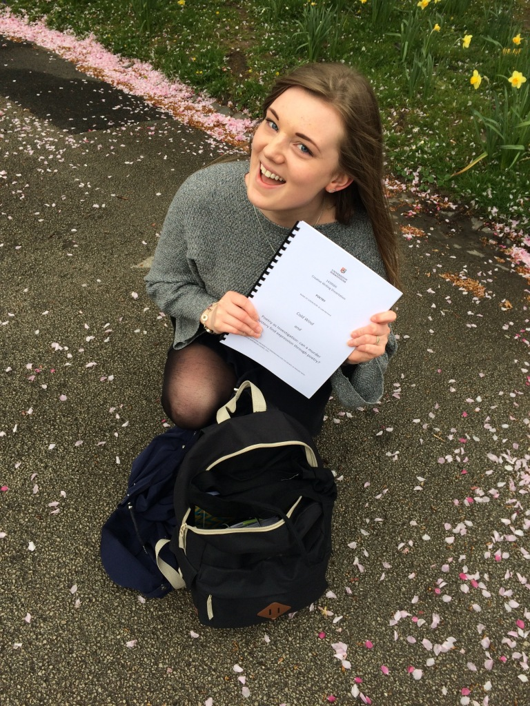 A young woman crouching on the concrete ground, which is covered in cherry blossoms. She is smiling up at the camera, holding a bound folder of paper, which has just been pulled from a black rucksack.