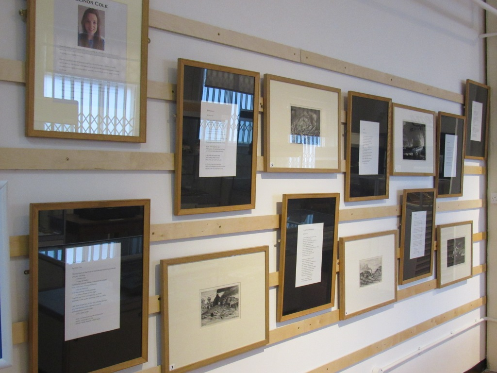 Thirteen frames, some with poems and others with black-and-white etchings of industrial Black Country scenes, are hung on a wall.