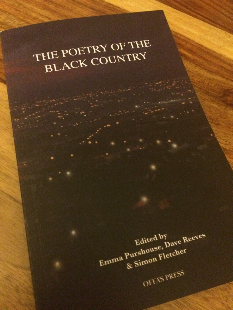 A book lying on a table, titled 'The Poetry of the Black Country: Edited by Emma Purshouse, Dave Reeves & Simon Fletcher: Offa's Press'. The cover is a painting: a dark violet shade with small specks of light, looking out over the Black Country region at night with the lights illuminating the landscape.