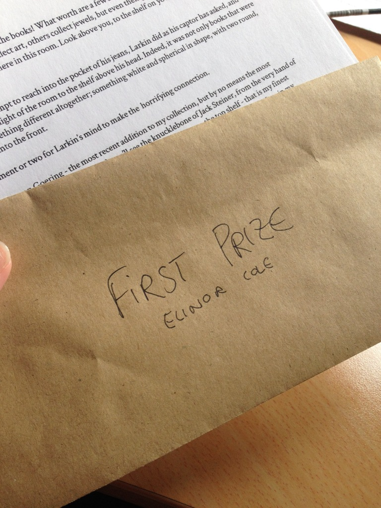 A brown envelope that reads 'First Prize Elinor Cole', held above a printed page of a short story.