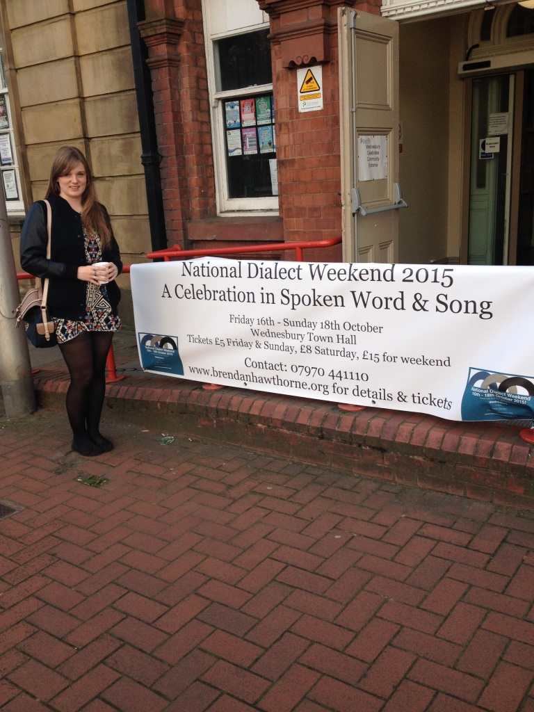 A young woman (Nellie Cole) stands smiling at the camera, next to a banner tied to the railings leading up to a town hall. The banner reads 'National Dialect Weekend 2015: A Celebration in Spoken Word and Song'.