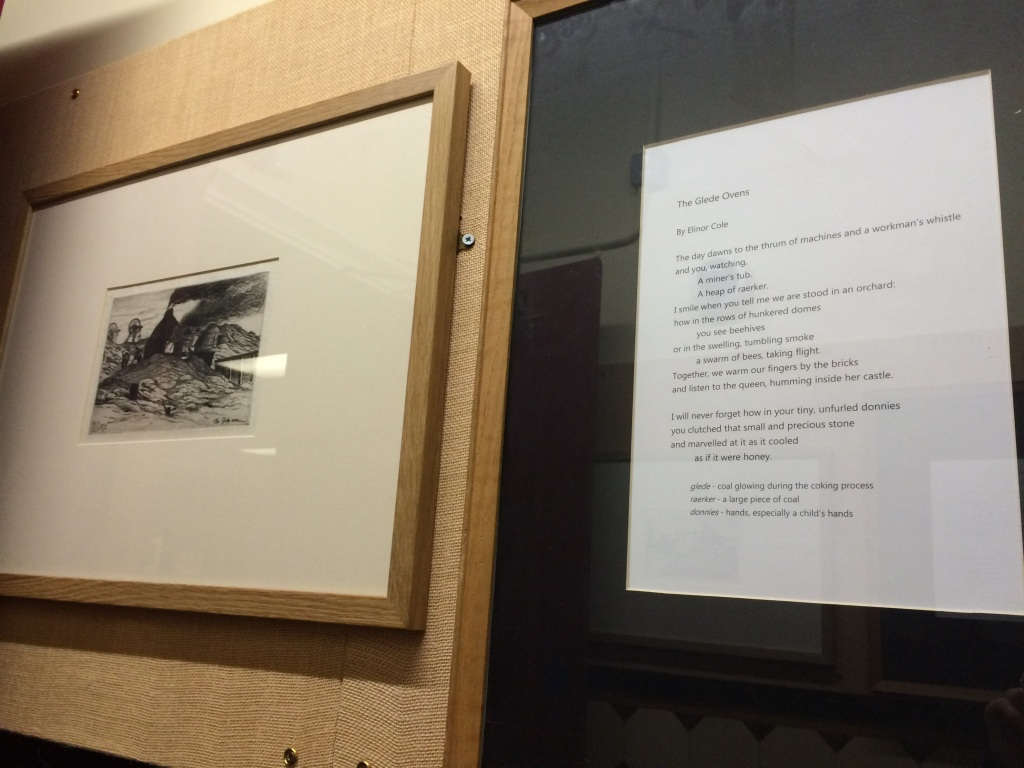 Two frames, one containing a black-and-white etching of brick domes with plumes of smoke coming from the chimney, the other with a poem titled 'The Glede Oven'. The frames hang on a wall.