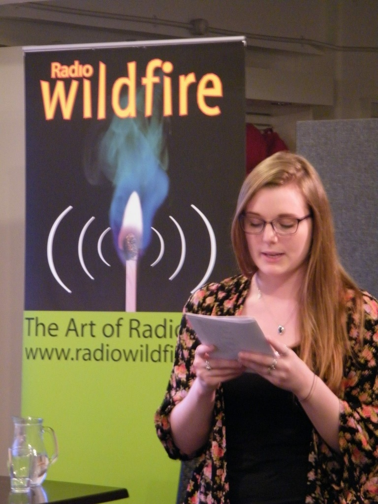 A young woman (Nellie) stands reading from a small booklet she holds in her hands. Behind her is a banner for 'Radio Wildfire'.