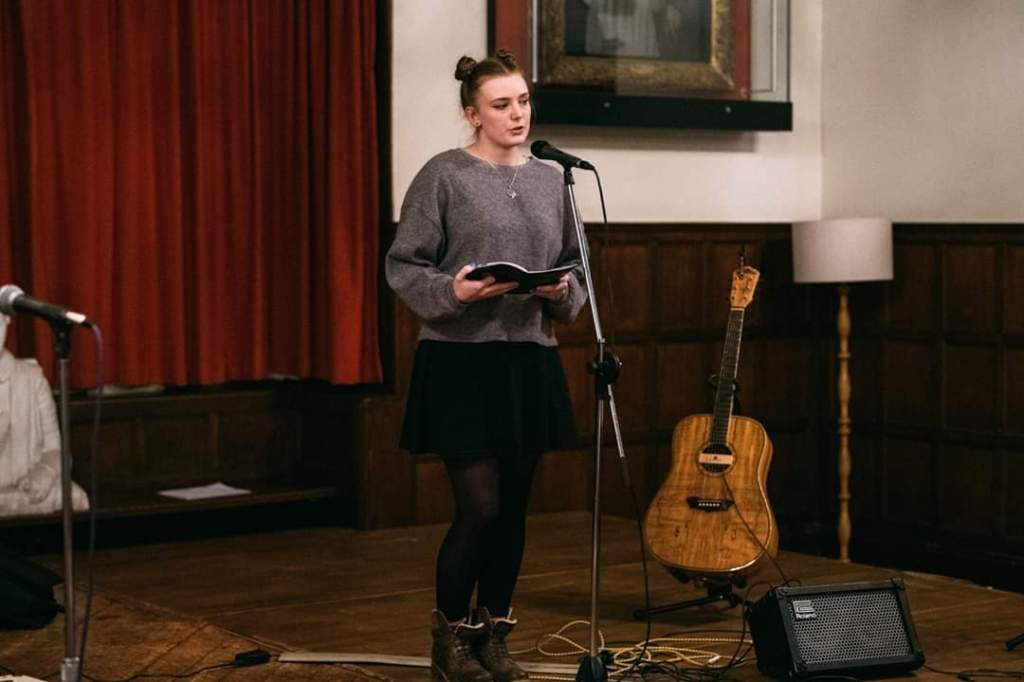 A young woman stands behind a mic, with a book in her hands. Behind her is a guitar propped up on a stand, various speakers on the stage floor, and a bust of Shakespeare in the background.