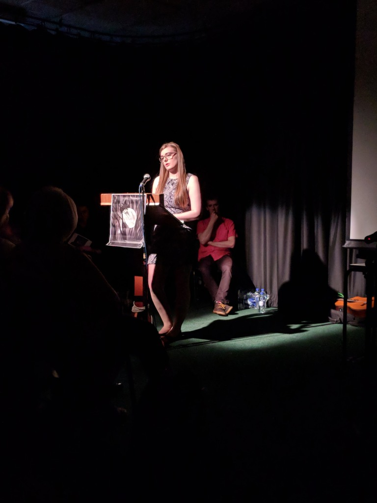 A young woman stands behind a podium, in a spotlight, reading to an audience out of shot.