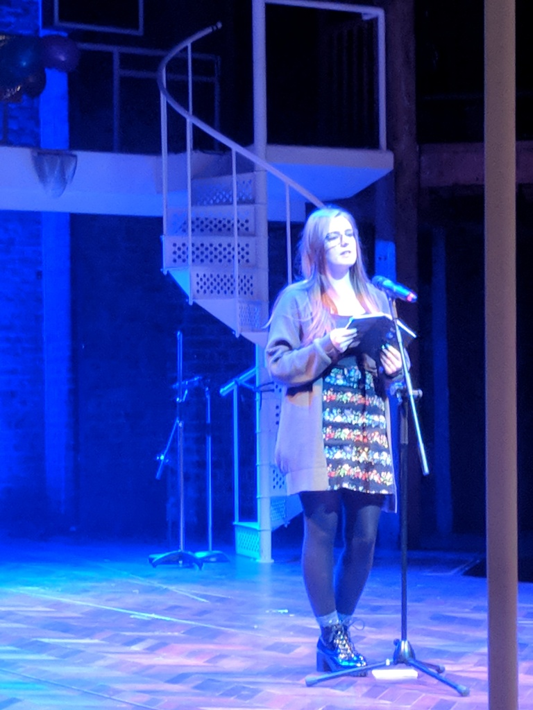 A young woman stands behind a mic on a theatre stage, holding a book in her hands.