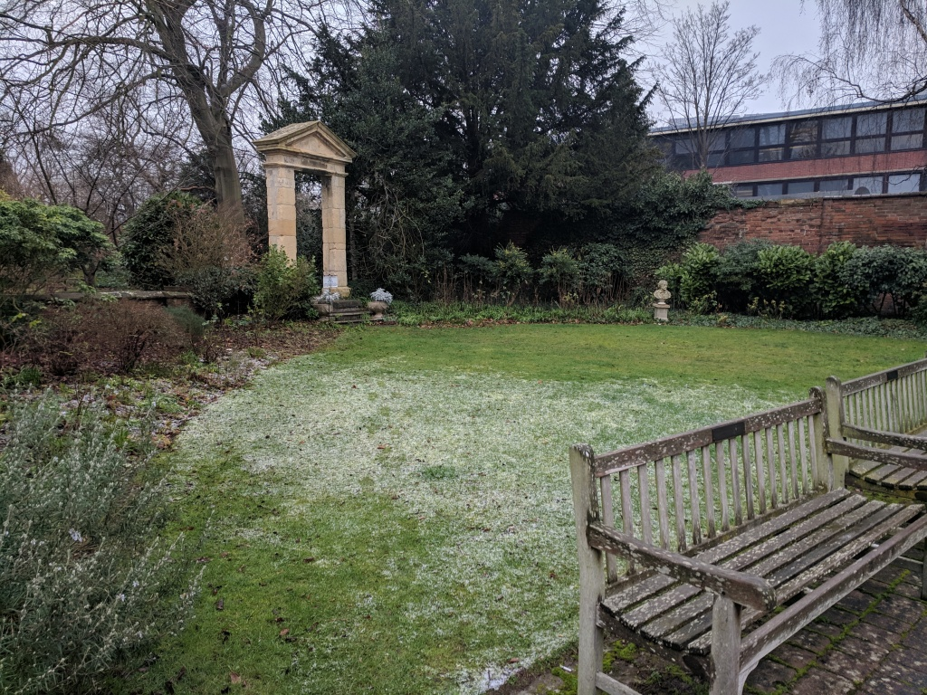 A triangular lawn, lightly dusted with frost. It is bordered by plants and trees, and a large stone archways at the apex.