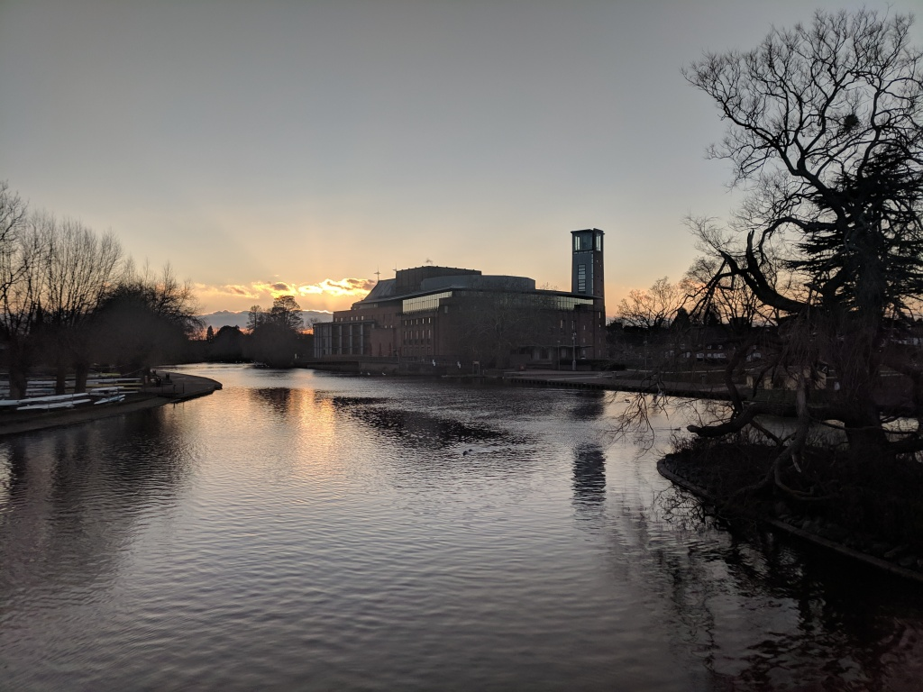 The Royal Shakespeare Theatre on the bank of the River Avon, silhouetted against a sunset sky.