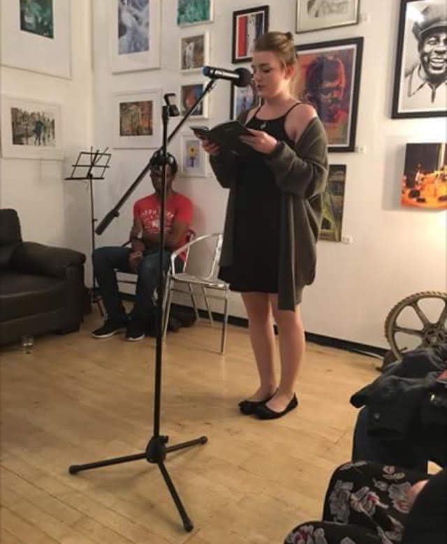 A young lady stands behind a mic, on a stand, reading from a book.